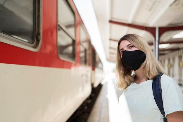 Vrouw die stoffenmasker draagt dat zich naast de trein bevindt Gratis Foto