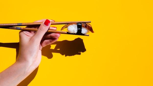 Vrouw die sushi in eetstokjes op gele achtergrond houdt Gratis Foto