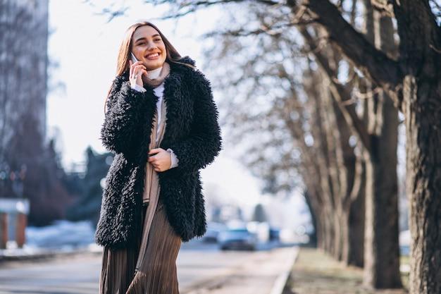 Vrouw die telefoon buiten de straat met behulp van Gratis Foto