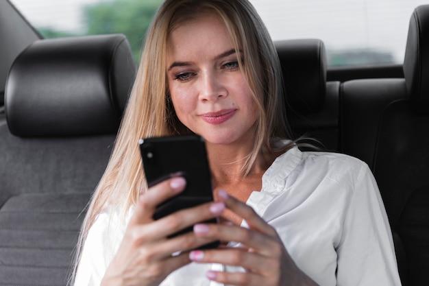 Vrouw die telefoon in achterbank controleert Gratis Foto