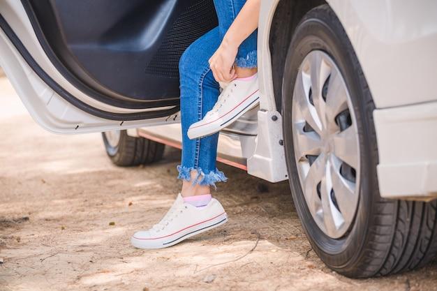 Vrouw die tennisschoenen in auto aan de kant van de weg zet Premium Foto