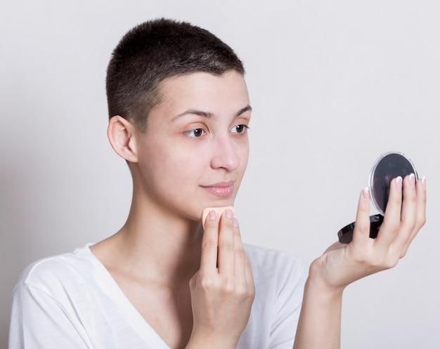 Vrouw die terwijl het bekijken zich in de spiegel schoonmaakt Gratis Foto