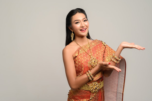 Vrouw die thaise kleding draagt die een handsymbool maakte Gratis Foto