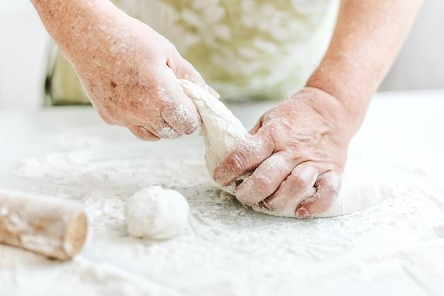 Vrouw die thuis deeg kneedt voor het koken van deegwarenpizza of brood. thuis koken concept. levensstijl Gratis Foto