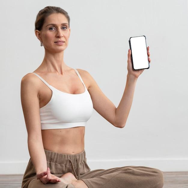 Vrouw die thuis yoga doet en smartphone houdt Gratis Foto