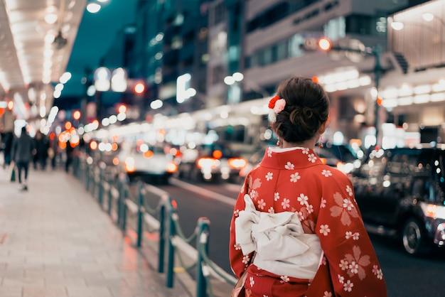 Vrouw die traditionele kimono op een straat in japan draagt Premium Foto