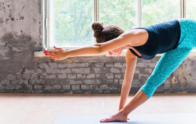 Vrouw die uitrekkende oefening op yogamat doet Gratis Foto