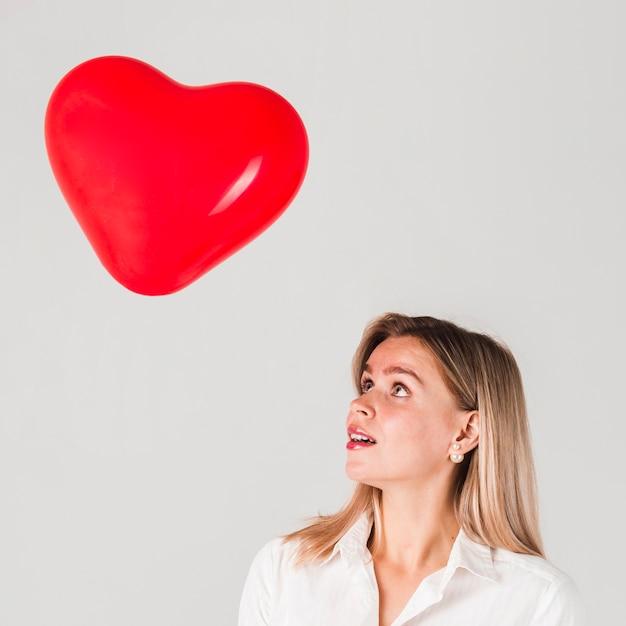 Vrouw die valentijnskaartenballon bekijkt Gratis Foto