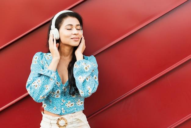 Vrouw die van de muziek op rode tinachtergrond geniet Gratis Foto