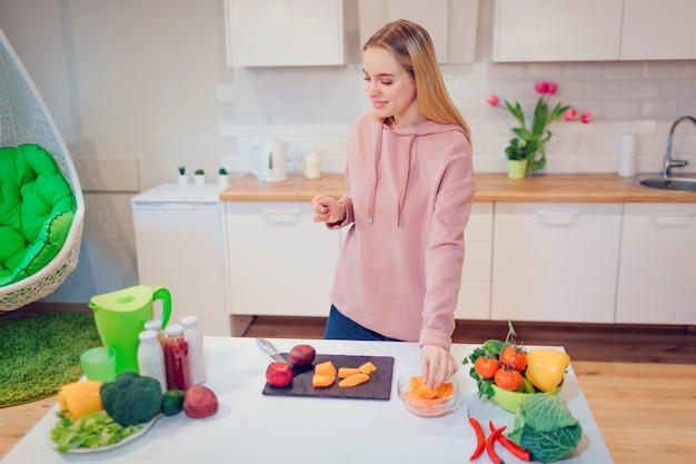 Vrouw die van het veganist de mooie blonde rauwe groenten in de keuken koken. Premium Foto