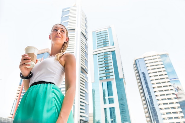 Vrouw die van koffie geniet om in metropolitaanse stad te gaan Premium Foto