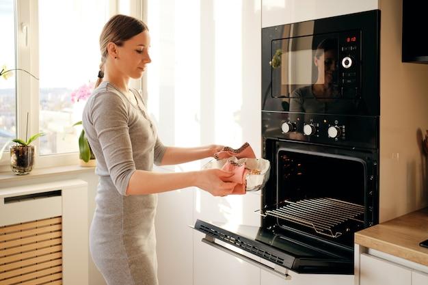 Vrouw die vers gebakken jem pastei uit oven nemen Gratis Foto