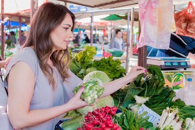 Vrouw die verse biologische groenten op straatmarkt koopt. lachende vrouw met groente in de winkel. concept van gezond eten winkelen Gratis Foto