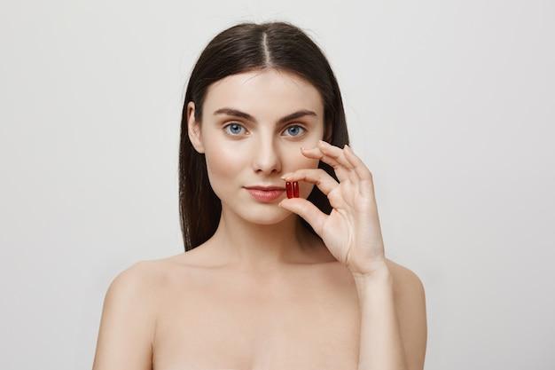 Vrouw die vitaminen toont, die voor gezondheid zorgt Gratis Foto