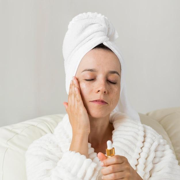 Vrouw die vochtinbrengende crème voor haar huid gebruikt Gratis Foto
