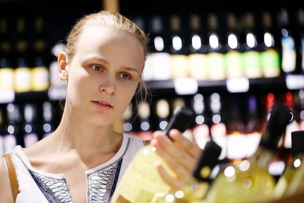 Vrouw die voor alcohol in een flessenopslag winkelt Premium Foto