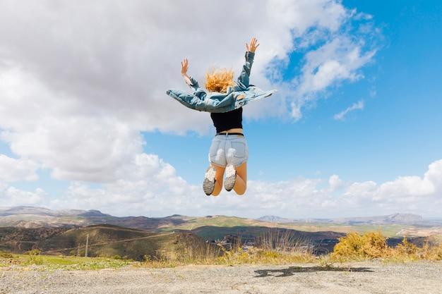 Vrouw die voor vreugde op heuveltop springt Gratis Foto