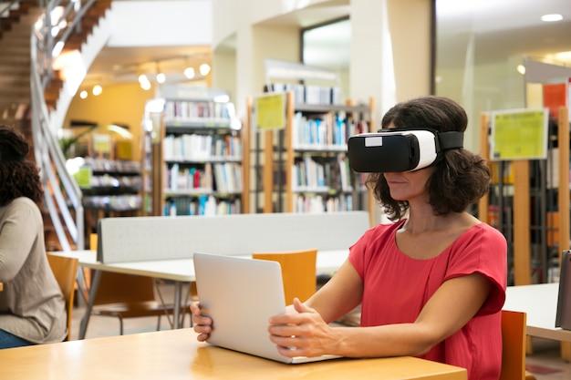 Vrouw die vr-simulator in bibliotheek gebruiken Gratis Foto