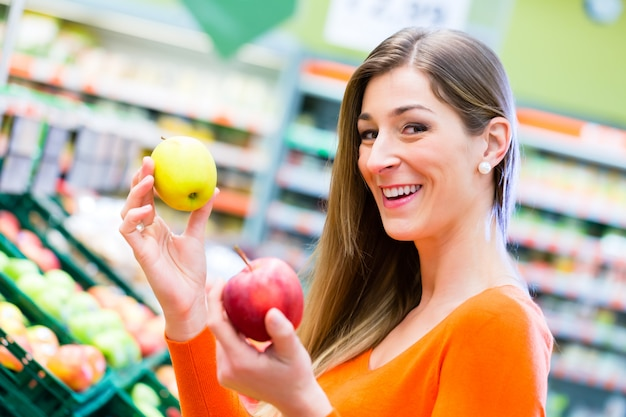 Vrouw die vruchten in supemarket selecteren Premium Foto