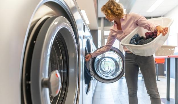 Vrouw die vuile kleren opnemen in de wasmachine in de wasruimte Premium Foto