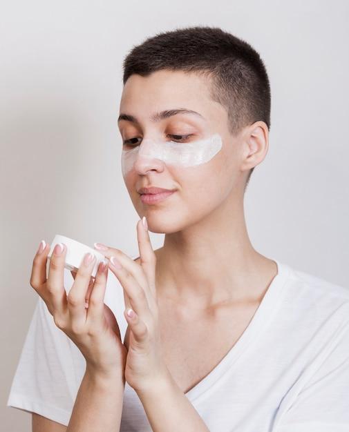Vrouw die wat gezichtscrème gebruikt om te hydrateren Gratis Foto