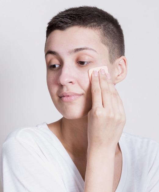 Vrouw die weg terwijl het schoonmaken van gezicht kijkt Gratis Foto