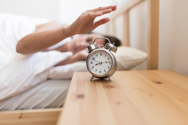 Vrouw die wekker uitzetten terwijl het liggen op bed Gratis Foto