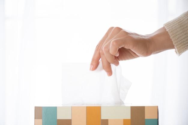 Vrouw die wit papieren zakdoekje van weefselvakje met de hand plukken. gezondheidszorg concept. Premium Foto