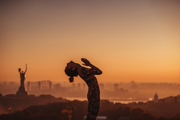 Vrouw die yoga op het dak van een wolkenkrabber in grote stad doet. Gratis Foto