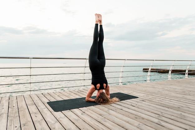 Vrouw die yoga op het strand doet en zich op haar handen bevindt Premium Foto
