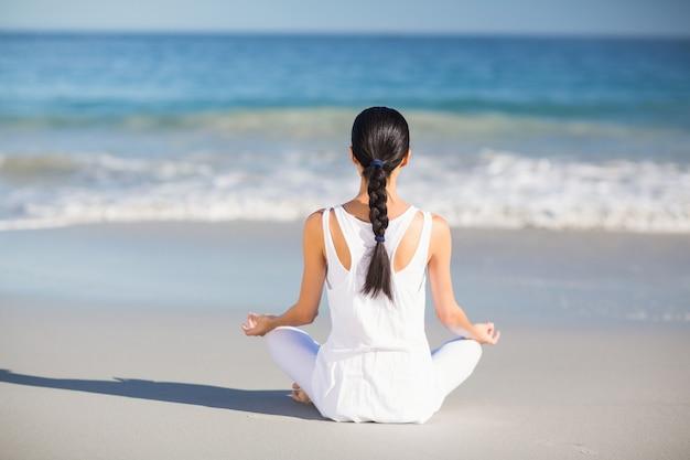 Vrouw die yoga uitvoert Premium Foto