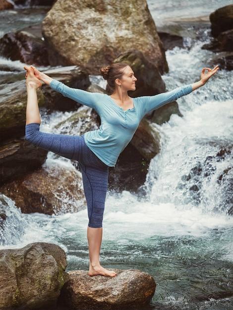 Vrouw die yogaasana natarajasana in openlucht doet bij waterval Premium Foto