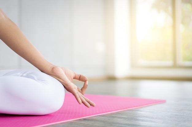 Vrouw die yogaoefening in de binnengymnastiek dicht omhoog met exemplaar ruimteachtergrond doet. concept van een goede gezondheid en welzijn. Premium Foto