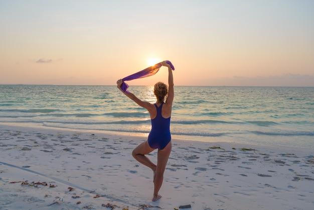 Vrouw die yogaoefening op de romantische hemel van het zandstrand uitvoert bij zonsondergang, achtermening, gouden zonlicht, echte mensen Premium Foto