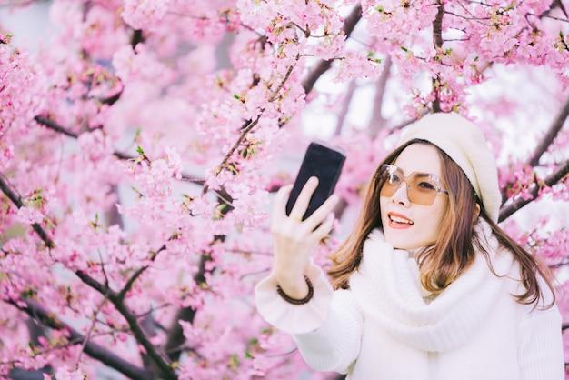 Vrouw die zelffoto in lentetijd met kersenbloesems nemen, sakura in japan Premium Foto