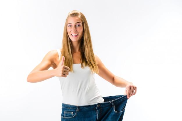 Vrouw die zich en een te grote broek bevindt na het verliezen van gewicht Premium Foto