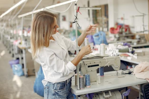 Vrouw die zich in de fabriek met een draad bevindt Gratis Foto
