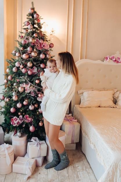 Vrouw die zich met baby dichtbij kerstmisboom bevindt. Premium Foto