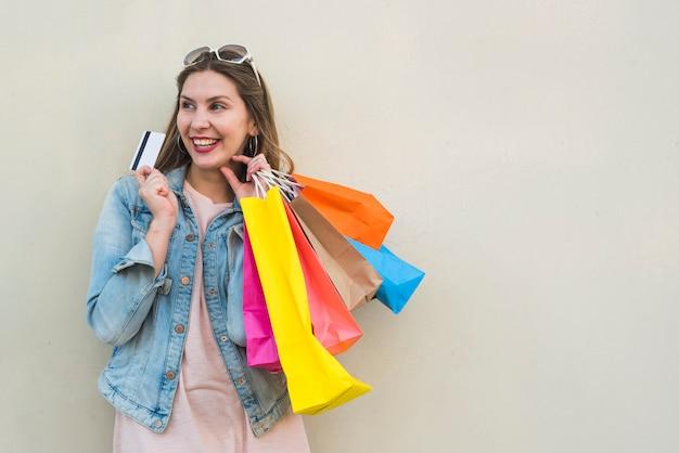 Vrouw die zich met het winkelen zakken en creditcard bij lichte muur bevindt Gratis Foto