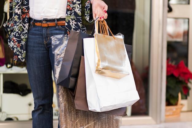 Vrouw die zich met het winkelen zakken in openlucht bevindt Gratis Foto