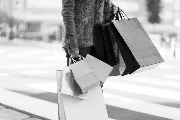 Vrouw die zich met het winkelen zakken op straat bevindt Gratis Foto