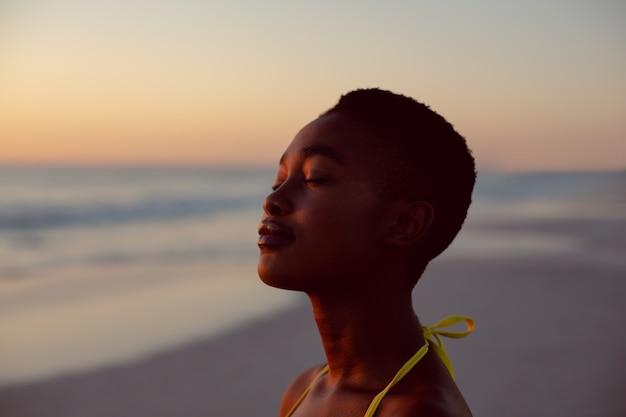 Vrouw die zich met ogen bevindt die op het strand worden gesloten Gratis Foto