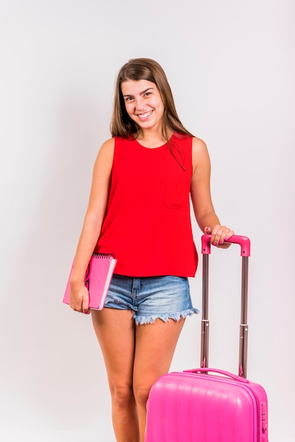 Vrouw die zich met roze koffer bevindt en notitieboekje houdt Gratis Foto