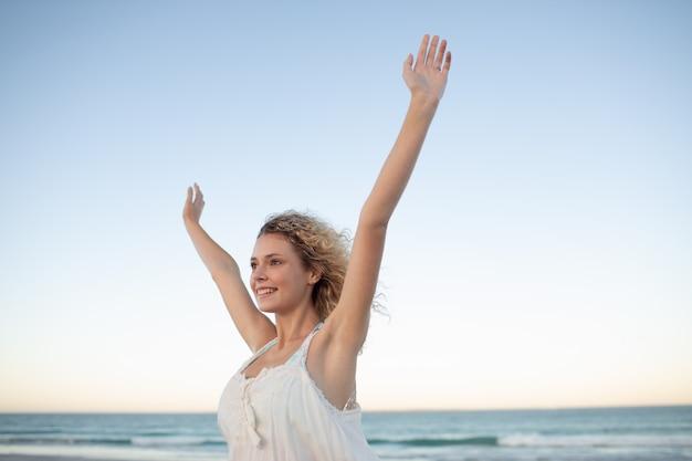 Vrouw die zich met wapens omhoog op het strand bevindt Gratis Foto