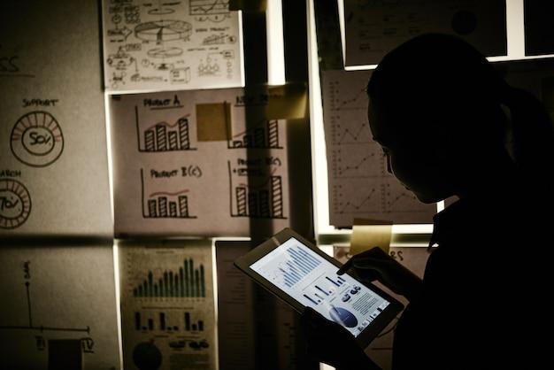 Vrouw die zich naast venster bevindt dat met bedrijfsgrafieken wordt behandeld en aan tablet werkt Gratis Foto