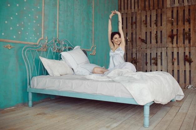Vrouw die zich uitstrekt in bed na wakker worden Gratis Foto