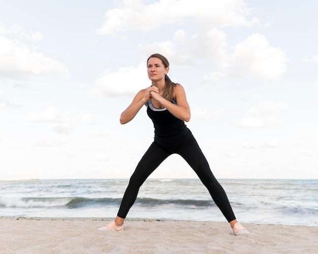 Vrouw die zich uitstrekt op het strand Gratis Foto
