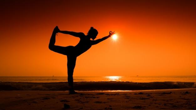 Vrouw die zich uitstrekt van haar lichaam in yoga stelt bij zonsondergang op het strand Gratis Foto