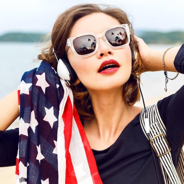 Vrouw die zich voordeed op het strand luisteren muziek in haar stijlvolle grote koptelefoon close-up Gratis Foto