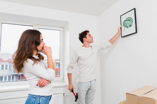 Vrouw die zijn vriend bekijkt die de omlijsting op witte muur hangt Gratis Foto